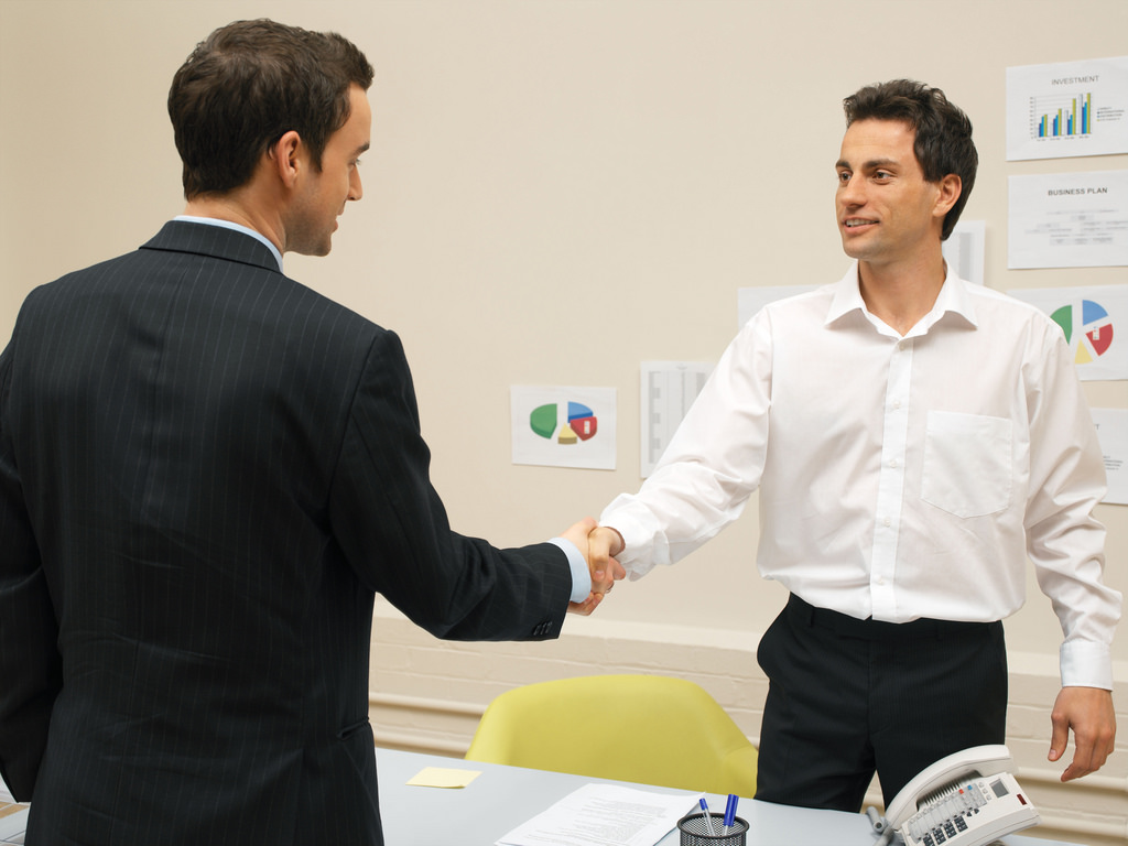 Two men shake hands in an office.