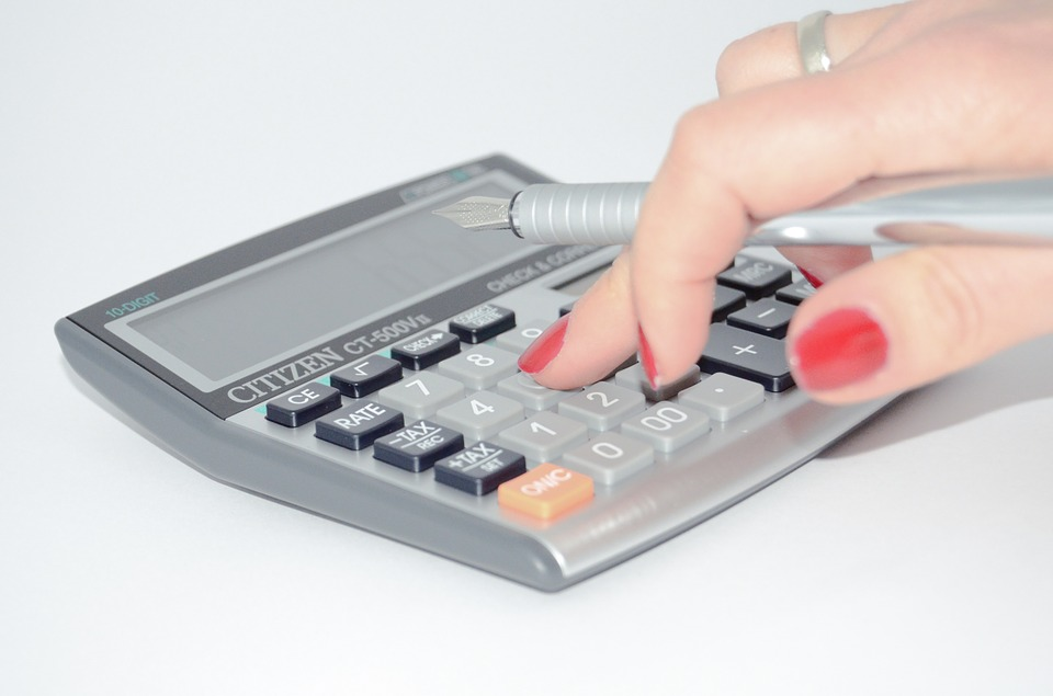 A person types on a calculator